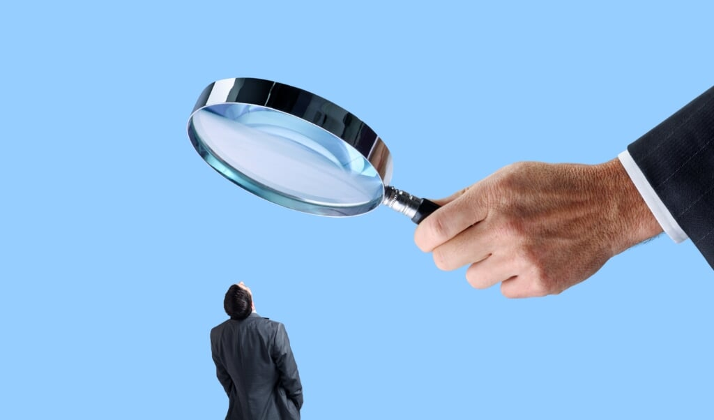 A businessman looks up at a large magnifying glass that is being held by an equally large hand isolated on a blue background.  (beeld iStock)