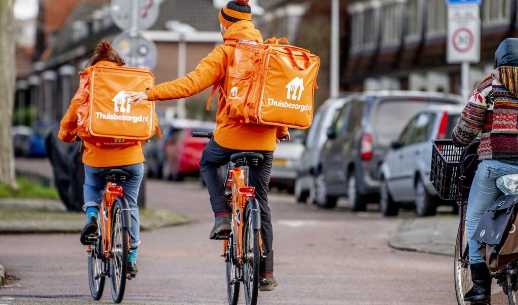 Maaltijdbezorgers van Thuisbezorgd onder weg op hun fiets.   (beeld anp / Robin Utrecht)