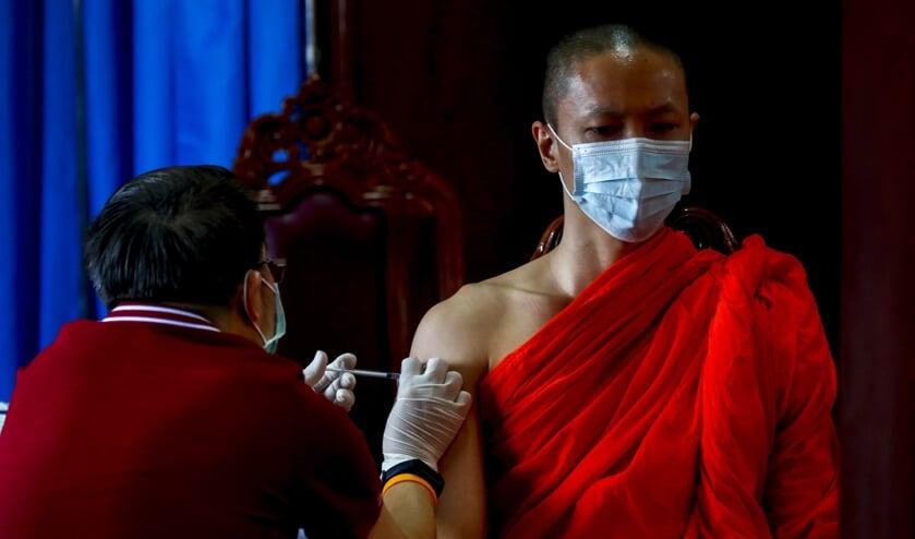 Een Boeddhistische monnik ontvangt het coronavaccin van AstraZeneca in Bangkok.  (beeld epa / Diego Azubel)