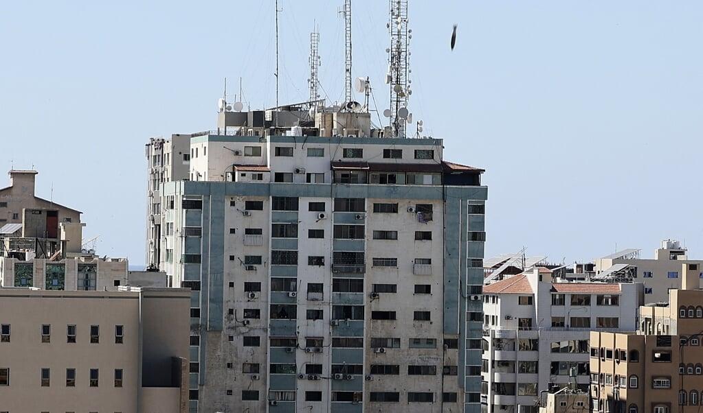 Een luchtaanval raakt de Al Jalaatoren, waarin ook redacties zitten van Al-Jazeera en the Associated Press.   (beeld afp / Mahmud Hams)