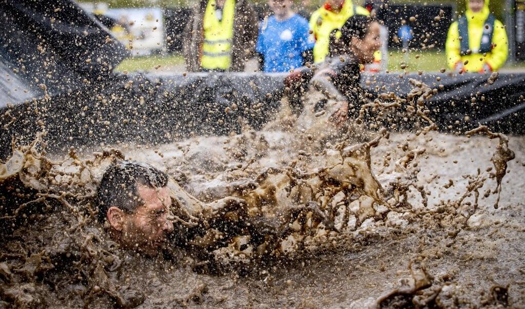 Een deelnemer duikt in ijskoud water tijdens het Fieldlab proefevenement Mud Masters.   (beeld anp / Sem van der Wal)