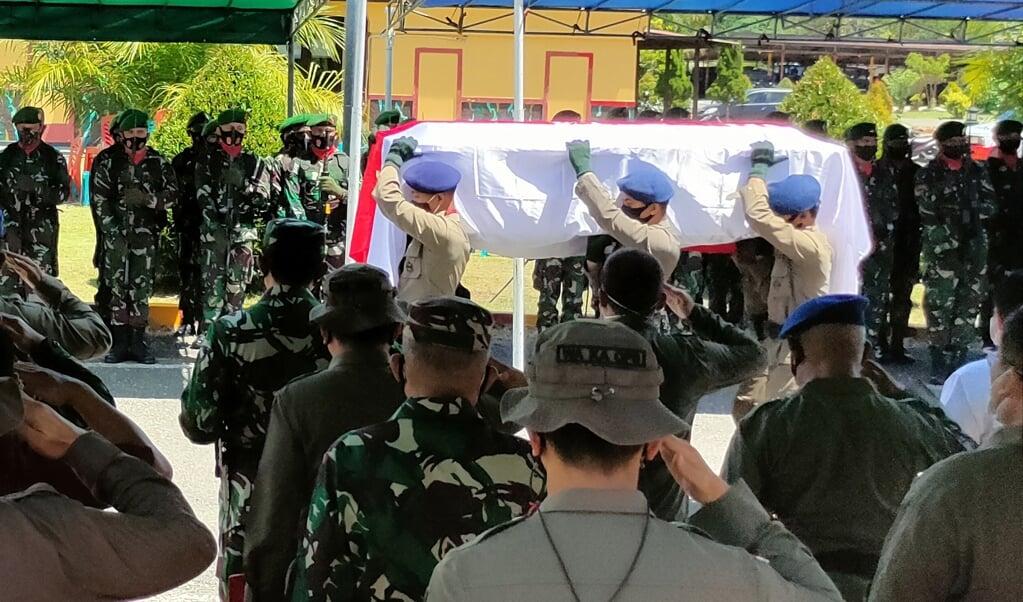Politieagenten dragen de kist van een van hun officieren die in een vuurgevecht met Papuastrijders is gedood.   (beeld afp / Saldi Hermanto)