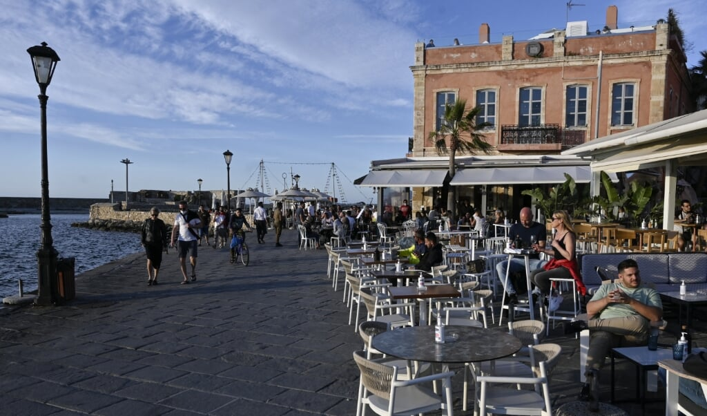 2021-05-13 22:37:35 Local and tourist sit at terraces and walk through the old town of Chania (La Canee) in the north west of the island of Crete, on May 13, 2021.  Greece easies the Covid-19 measures in welcoming international tourists on May 14. Louisa GOULIAMAKI / AFP  (beeld Greece Easies the Covid-19 Measures in Welcoming International Tourists on may 14. louisa Gouliamaki / afp)