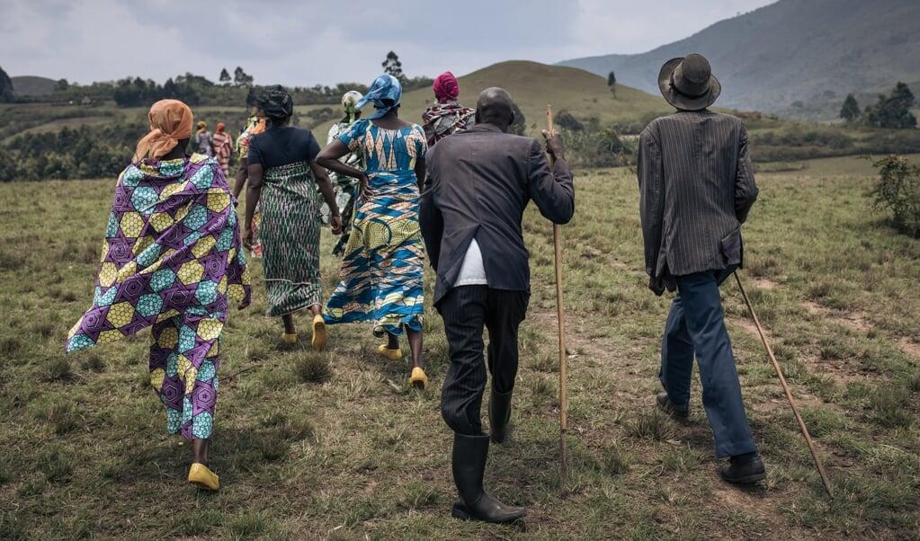 Mannen en vrouwen van de Banyamulenge zijn op weg naar de begrafenis van een herder die werd vermoord door militanten in de buurt van Minembwe in Zuid-Kivu.  (beeld afp / Alexis Huguet)