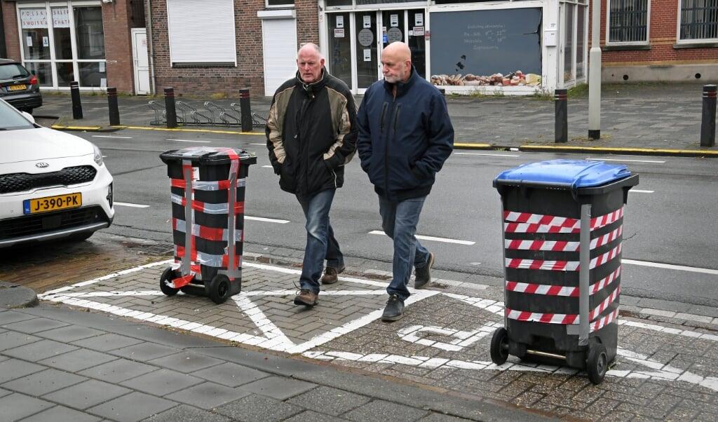 Andy Knobel (l.) en Barro Wijkmans tussen de kliko's tegen wildparkeerders.  (beeld Marcel van den Bergh)