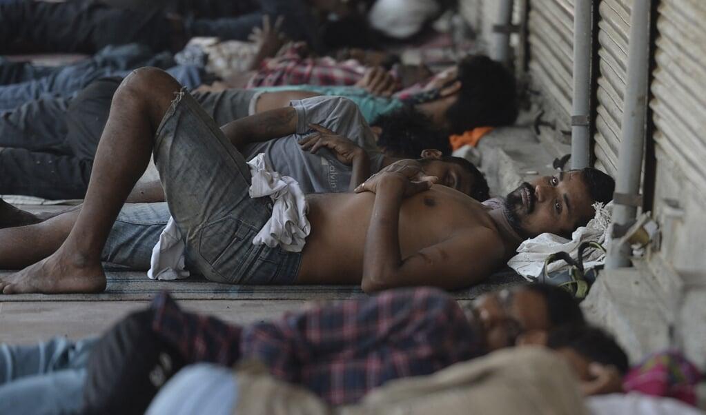 Indiase arbeiders rusten uit voor winkels in New Delhi die door de coronalockdown gesloten zijn.  (beeld afp / Arun Sankar)