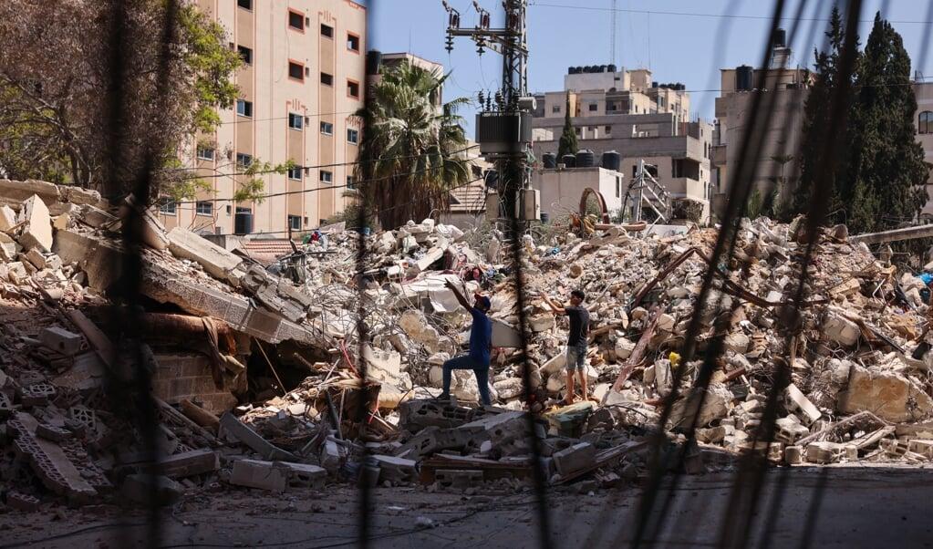Palestijnse mannen staan naast een gebouw dat de dag ervoor werd vernietigd tijdens Israëlische luchtaanvallen.  (beeld afp / Mohammed Abed)