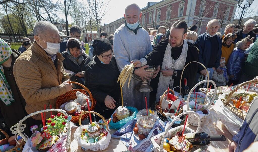 Een Russisch-orthodoxe priester zegent de paastaarten en -eieren die gelovigen op lange tafels hebben neergezet. Gisteren en vandaag is de viering van Pasen in de Oosters-Orthodoxe Kerk.  (beeld epa / Sergei Ilnitsky)