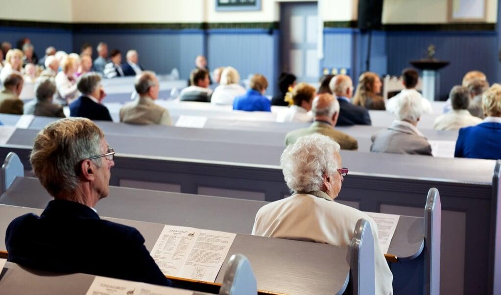 Kerkgangers wonen op zondagochtend een kerkdienst bij in De Lier, voor de coronacrisis.  (beeld anp / Xtra Roos Koole)