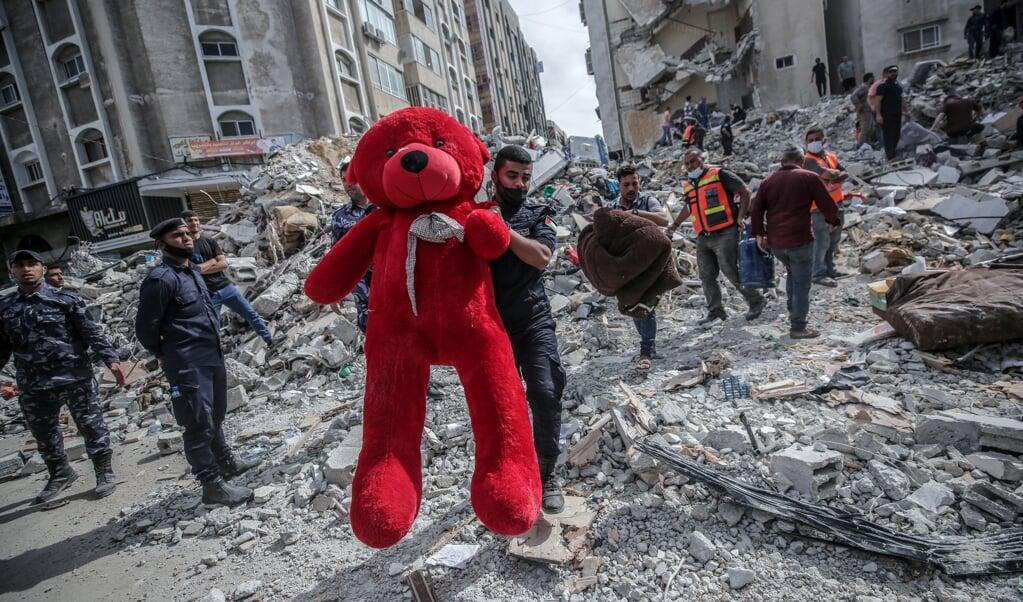 Een Palestijn tilt een teddybeer uit het puin in Gaza-stad. De onlusten tussen Joden en Arabieren binnen Israël zijn, veel meer dan het Gaza-front, de sleutel om het Palestijns-Israëlisch conflict te begrijpen.  (beeld epa / Mohammed Saber)