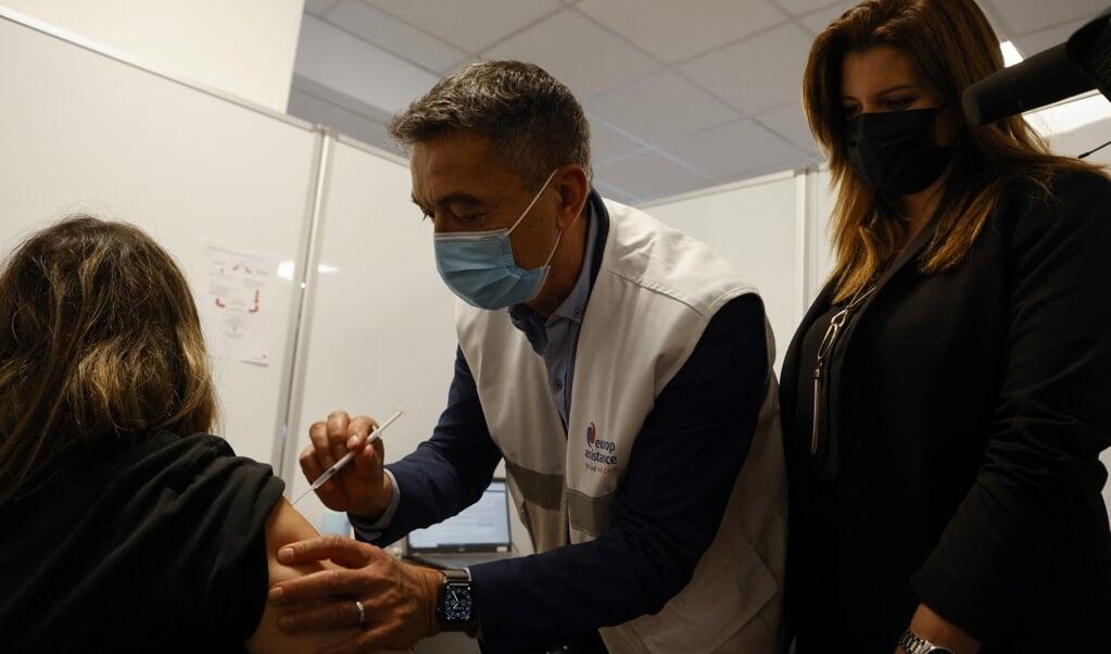 De Franse onderminister van Burgerschap Marlene Schiappa kijkt toe als een zwangere vrouw in Parijs wordt gevaccineerd in het kader van een voorrangsregeling.  (beeld afp / Ludovic Marin)