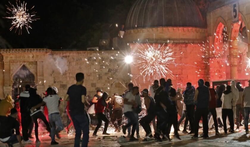 Bij de onlusten werd gegooid met stenen en werden flitsgranaten afgevuurd.  (beeld afp / Ahmad Gharabli)