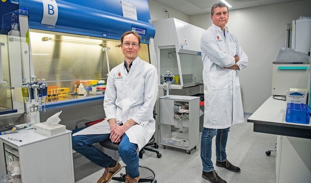Wetenschappers Jeroen den Dunnen (links) en Menno de Winther in het laboratorium van het Amsterdam UMC. Door hun onderzoek kunnen heftige reacties op het coronavirus mogelijk worden afgezwakt.  (beeld Guus Dubbelman)