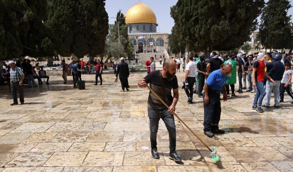 Palestijnen maken het plein voor de Al-Aqsa moskee schoon op maandag 10 mei nadat Palestijnen en de Israëlische politie er opnieuw slaags waren geraakt. Maandag raakten opnieuw 300 mensen gewond tijdens de escalerende conflicten.  (beeld afp / Ahmad Gharabli)