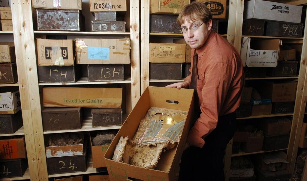 Dirk Obbink in de universiteitsbibliotheek van Oxford met een Egyptisch mummiemasker, gemaakt van papyrus, in 2005.  (beeld Geraint Lewis)