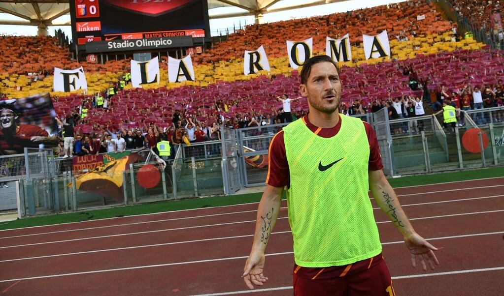 'Totti is Rome', leest het spandoek achter Francesco Totti. In mei 2017 nam hij afscheid van de fans.  (beeld Vincenzo Pinto / afp)