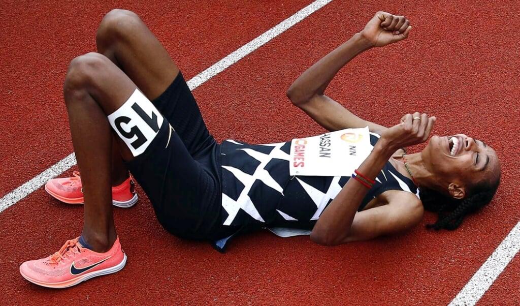 Sifan Hassan laat zich op de grond vallen na haar record op de 10.000 meter.  (beeld epa / Vincent Jannink)