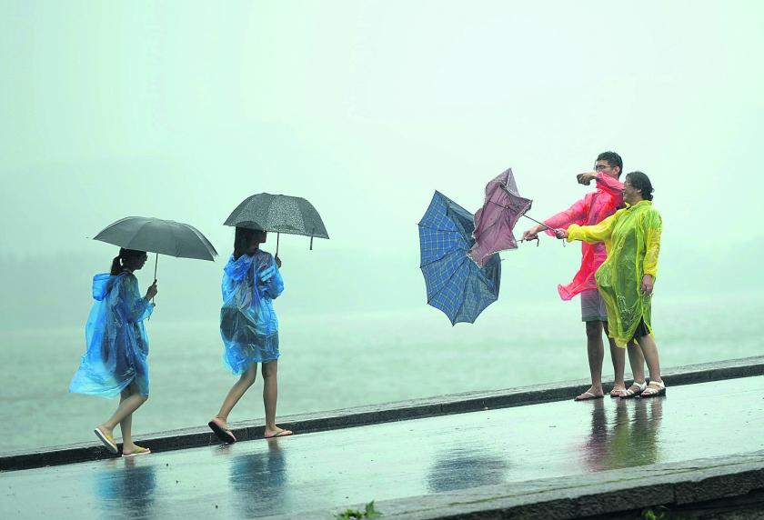 beeld ap / chinatopix Toeristen in het Chinese Hangzhou kunnen nog wel lachen om hun omgewaaide paraplu's.  Maar zo'n 1,1 miljoen men..  (ap / chinatopix)