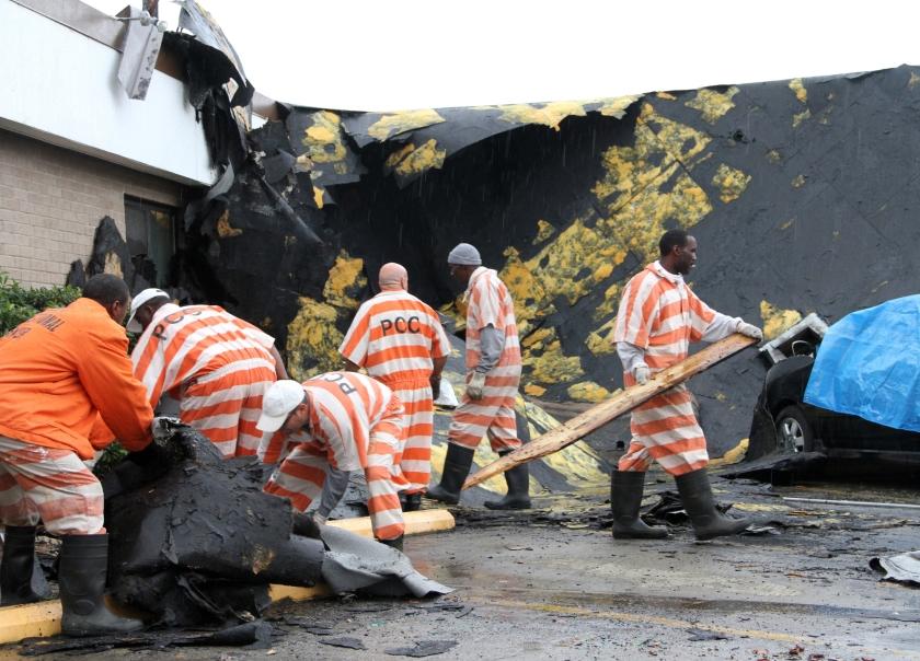 Gedetineerden helpen mee om de schade van een tornado op te ruimen.  (ap / Meredith Blinder)