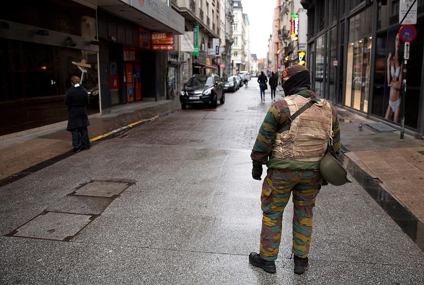 Een Belgische militair patrouilleert door een vrijwel verlaten winkelstraat in Brussel.  De Belgische regering verhoogde zaterdag het terreuralarm naar het hoogste dreigingsniveau, omdat gevreesd werd voor aanslagen in Brussel, vergelijkbaar met die in Parijs een week geleden  (ap / Thierry Monasse)