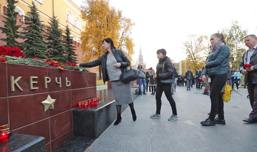 Als teken van rouw om de bij de schietpartij op de school in Kertsj omgekomen studenten en andere slachtoffers, leggen mensen bloemen op het heldenmonument in de stad op de Krim.  (epa / Maxim Shipenkov)