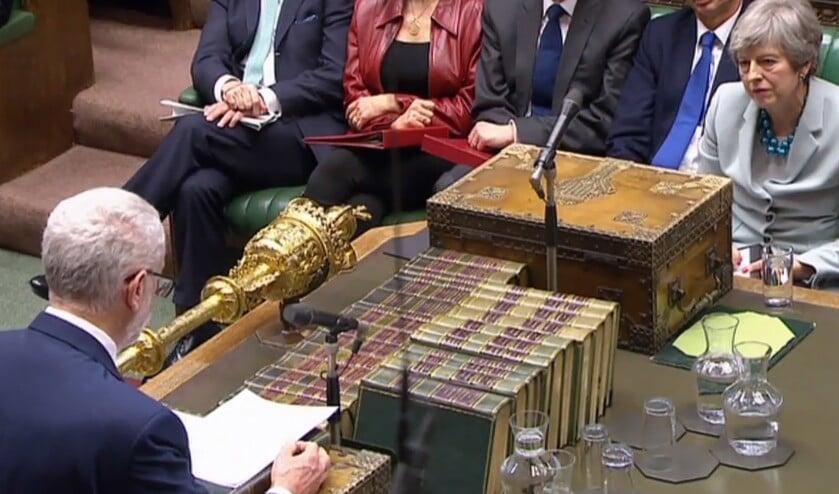 De Britse premier Theresa May luistert naar oppositieleider Jeremy Corbyn, terwijl die in het Lagerhuis spreekt over het brexitproces.  (afp)