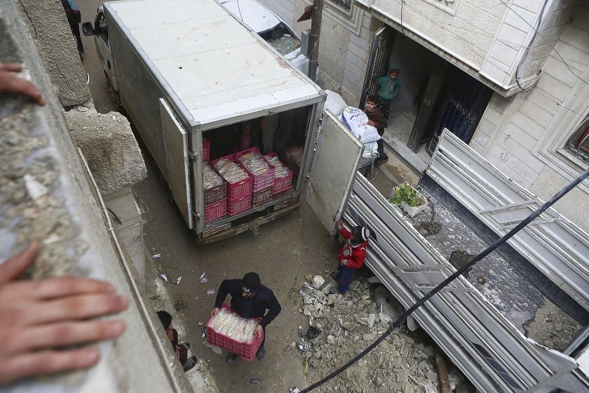 Vrijwilligers helpen in Douma en Oost-Ghouta met het uitdelen van humanitaire goederen na luchtaanvallen door Syrische en Russische vliegtuigen. De belegerde stadswijken in Damascus zijn in handen van rebellenmilities.  (ap / Samer Bouidani)