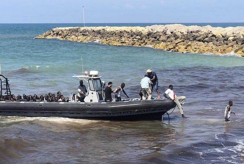 Afrikanen die op de Middellandse Zee van een beschadigde rubberboot zijn gered, worden in Libië aan wal gebracht.  (ap / libische kustwacht)