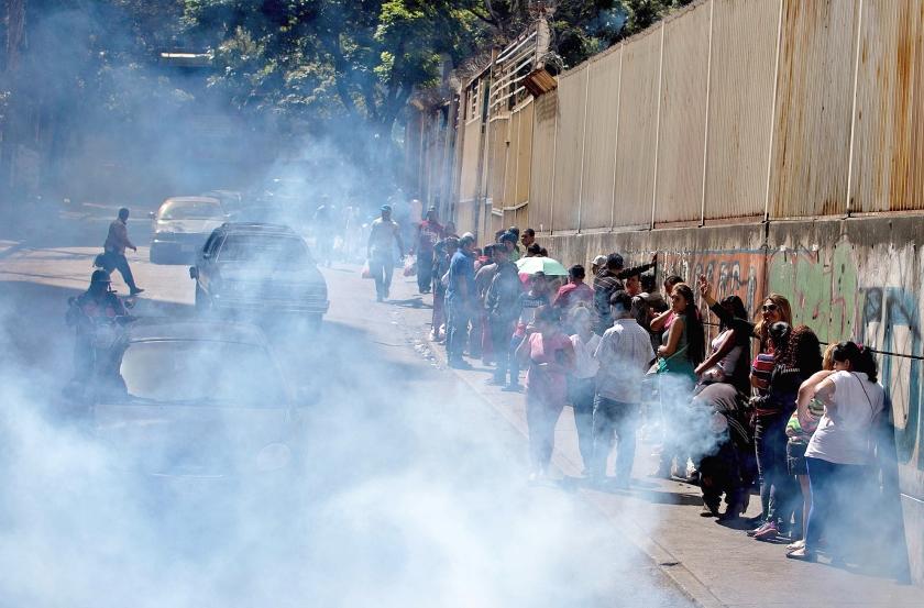 Mensen in de Venezolaanse hoofdstad Caracas staan in de rij voor ontsmettingsmiddelen, die door de overheid gratis worden verstrekt.  (ap / Fernando Llano)
