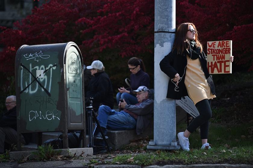 Een vrouw protesteert in Pittsburgh tegen het bezoek van president Donald Trump en zijn vrouw Melania, die hun medeleven willen betuigen na de aanslag van zaterdag in de synagoge daar.  (afp / Brendan Smialowski)