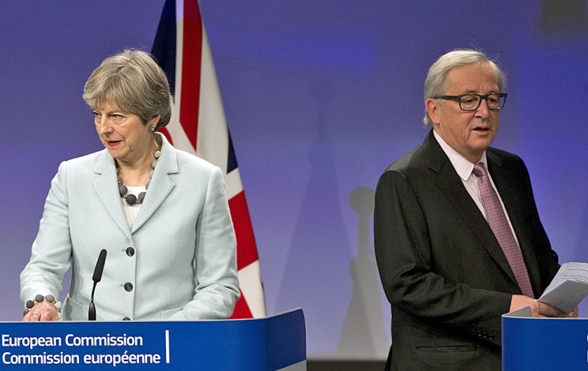 De Britse premier Theresa May en voorzitter Jean-Claude Juncker van de Europese Commissie, vrijdag bij de bekendmaking van het deelakkoord.  (ap / Virginia Mayo)