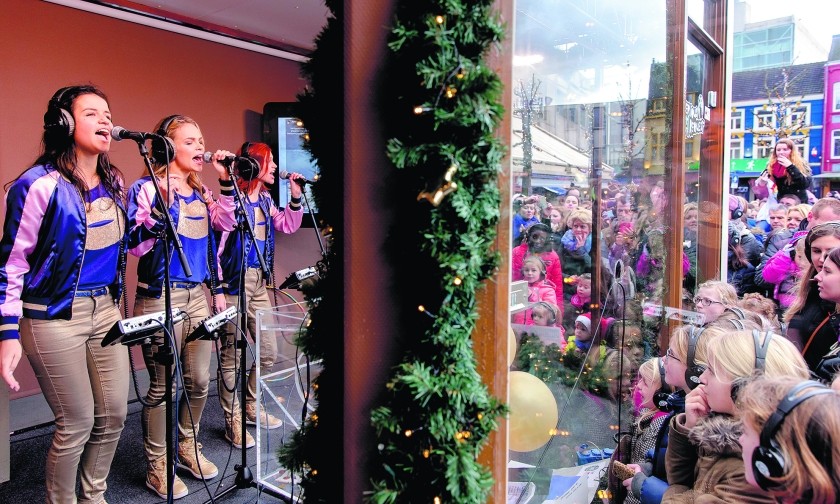 Popgroep K3 zingt in het Glazen Huis, waar drie dj's opgesloten zitten.  (nd en anp / Sander Koning)