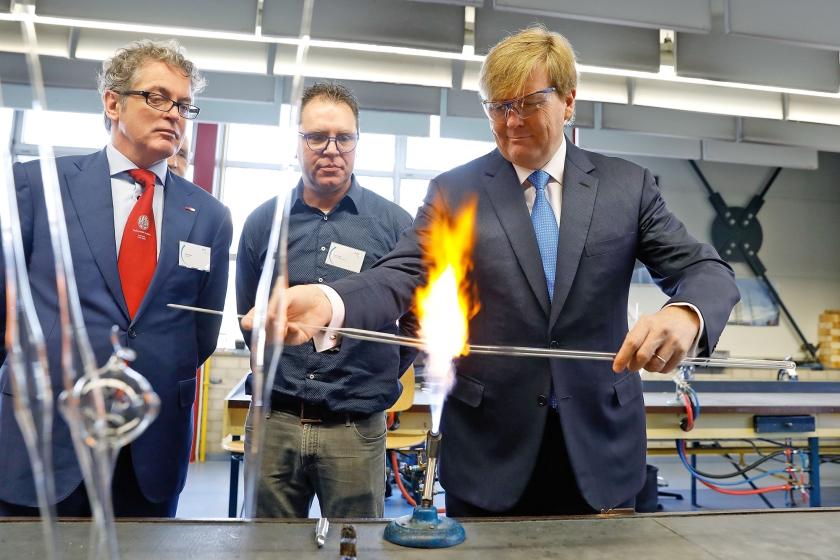 Koning Willem-Alexander (r.) steekt bij de opening van de nieuwe vleugel van de Leidse instrumentmakers School ook zelf de handen uit de mouwen.  (Dick den Braber en anp / Bas Czerwinski)