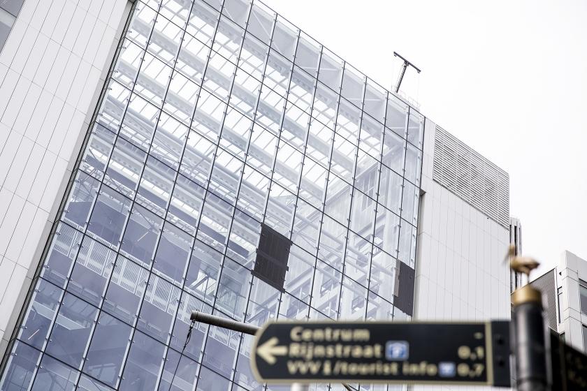 Het veiligheidsglas van vier ramen van het gebouw waarin de ministeries van Buitenlandse Zaken en Infrastructuur en Waterstaat huizen, vertoont barsten. Uit voorzorg is daarom een glasplaat weggehaald en zijn de drie andere afgedekt.  (anp / Laurens van Putten)