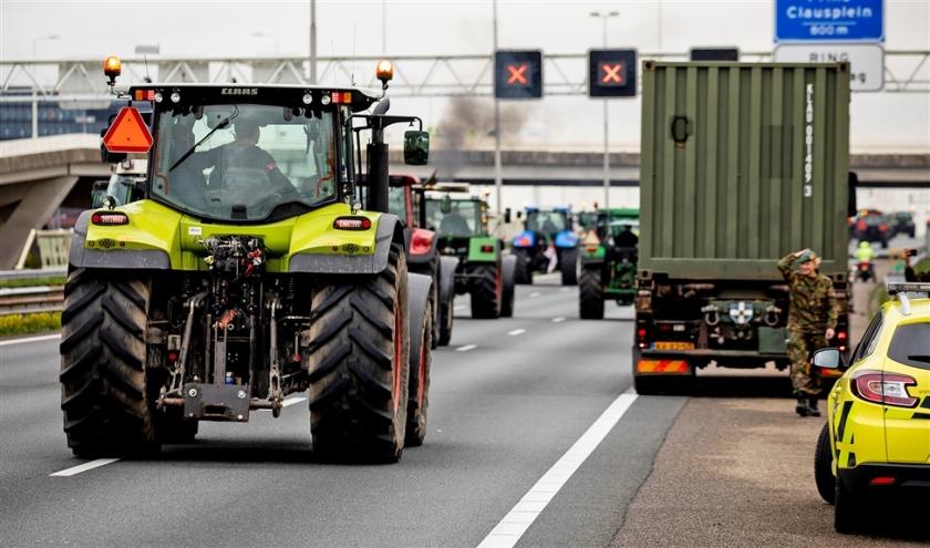 Boeren rijden met hun tractoren door de afsluiting van Defensie heen op de A12 bij Nootdorp.  (anp / Sem van der Wal)