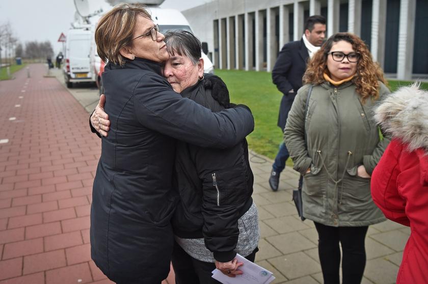 De moeder van Mitch Henriquez neemt afscheid van familieleden buiten de rechtbank op Schiphol, nadat die twee agenten die Henriquez arresteerden, schuldig had verklaard aan mishandeling, met de dood tot gevolg.  (Marcel van den Bergh)
