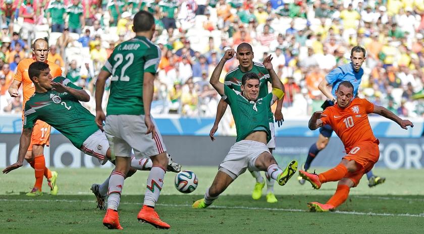 Wesley Sneijder haalt uit in de achtste finale op het WK voetbal in 2014 tegen Mexico. Oranje stond in die wedstrijd lang op achterstand. In de 88e minuut maakte Sneijder de gelijkmaker, waarna Nederland uiteindelijk met 2-1 won.  (ap / Natacha Pisarenko)