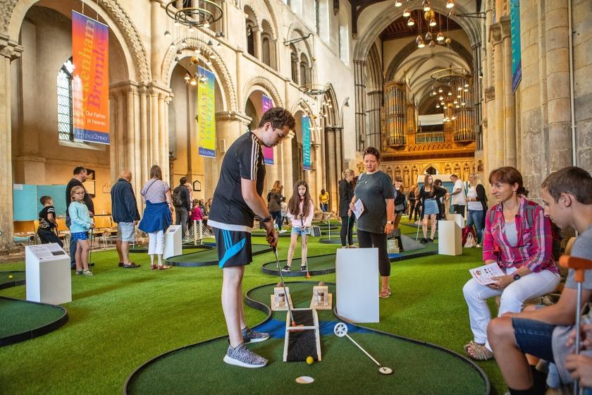Bezoekers van de middeleeuwse kathedraal van Rochester leven zich uit op de minigolfbaan van negen holes, op de plek waar anders de congregratie zit.  (Antonio Olmos)