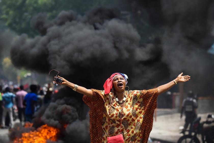 Een deelneemster roept leuzen tegen de regering, tijdens een betoging in de Haïtiaanse hoofdstad Port-au-Prince. Volgens de betogers is de regering corrupt.  (afp / Chandan Khanna)