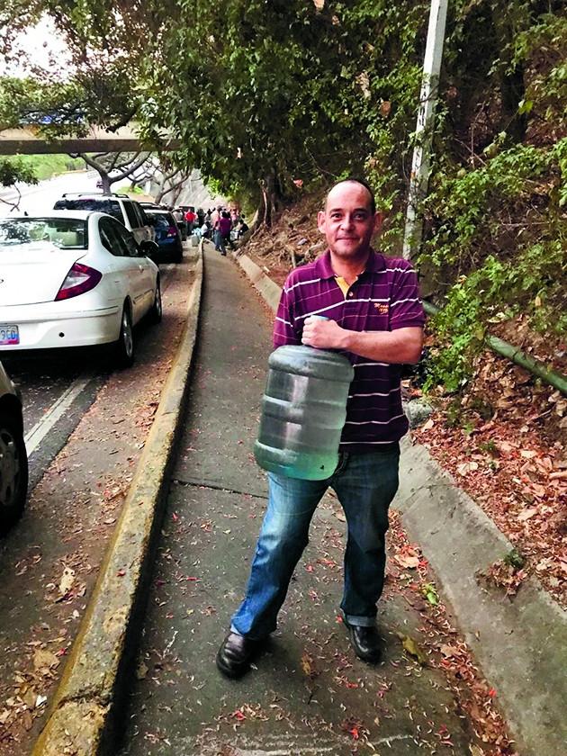 Andres Moreno zit door de stroomstoring thuis zonder water.   (afp / Federico Parra en vk)