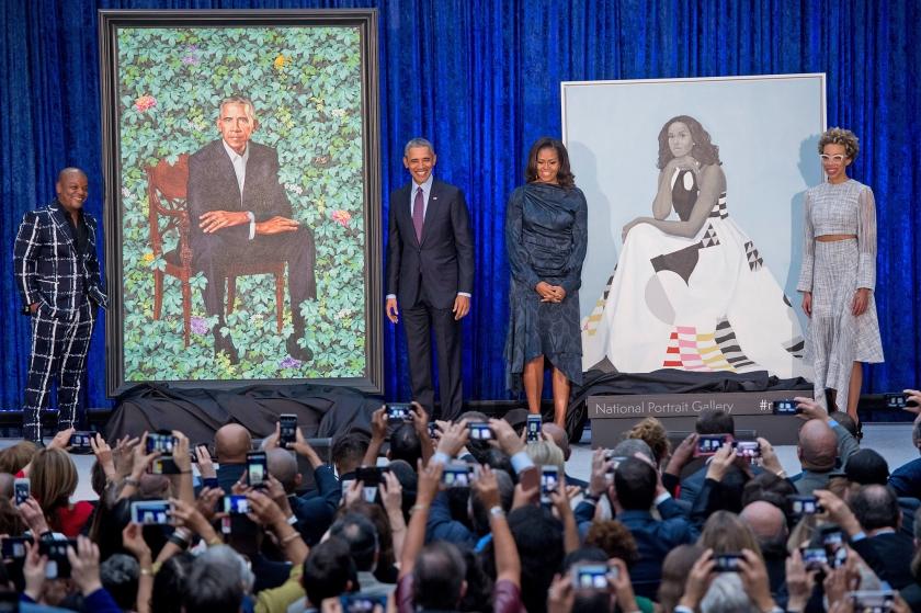Barack Obama en zijn vrouw Michelle bij hun portretten en geflankeerd door de artiesten die ze maakten, Kehinde Wiley (links) en Amy Sherald (rechts).  (afp / Saul Loeb)