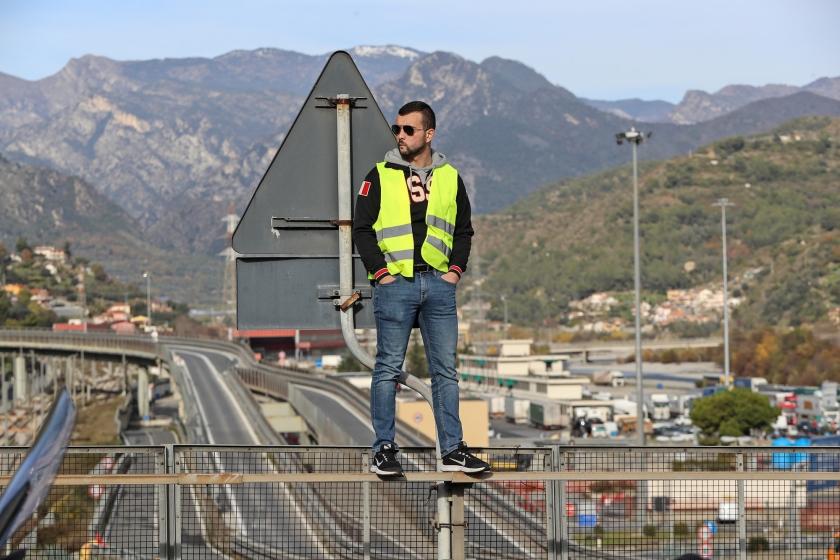 Een demonstrant met een geel vest staat op een brug tijdens een demonstratie op 22 december 2018 in Ventimiglia, bij de Frans-Italiaanse grens. De demonstratie was gericht tegen het beleid van president Emmanuel Macron.  (afp / Valéry Hache)
