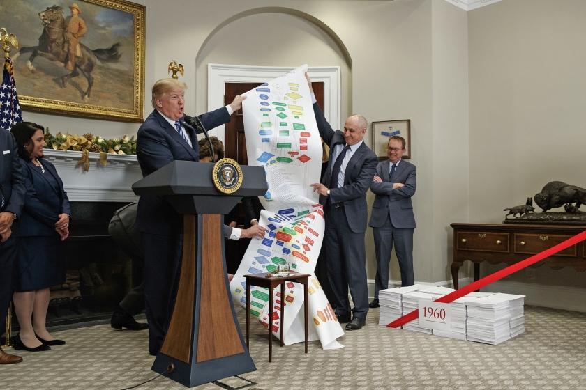 President Trump houdt een lijst omhoog met regelgeving over snelwegen, tijdens een bijeenkomst over het inperken van overbodige regels en wetten.  (ap / Evan Vucci)