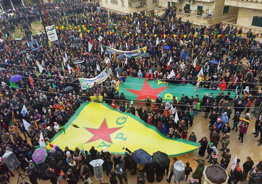Koerden die in Afrin betogen tegen Turkse bedreigingen zwaaien met vlaggen van de YPG en andere partijen.  (ap)