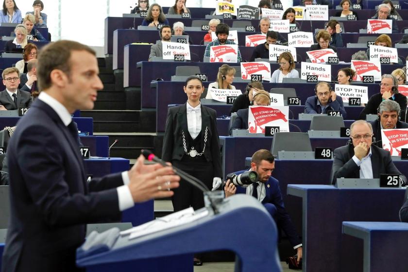 Terwijl Macron spreekt, tonen Europarlementariërs borden met 'Stop de oorlog in Syrië', uit protest tegen de recente Amerikaans-Brits-Franse luchtacties.  (ap / Jean François Badias)
