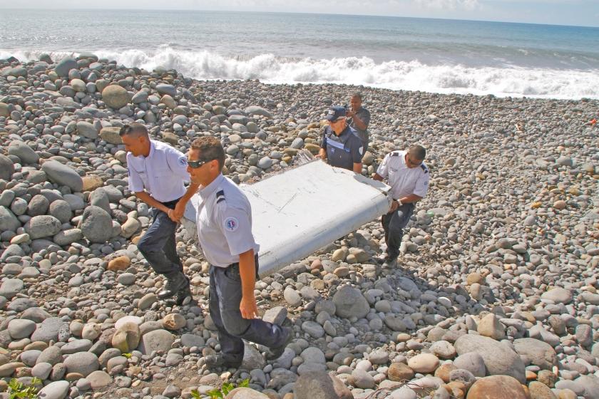 Franse agenten op het eiland Réunion dragen een wrakstuk van MH370 weg. Het werd in juli 2015 gevonden.  (ap / Lucas Marie)