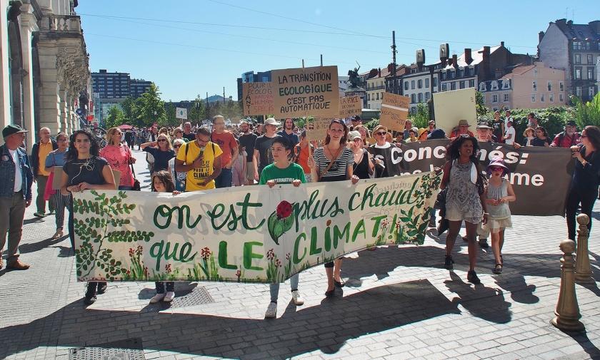 'Wij zijn heter dan het klimaat' staat op een spandoek dat bij de mars in Clermont-Ferrand werd meegedragen.  (Imco Lanting)