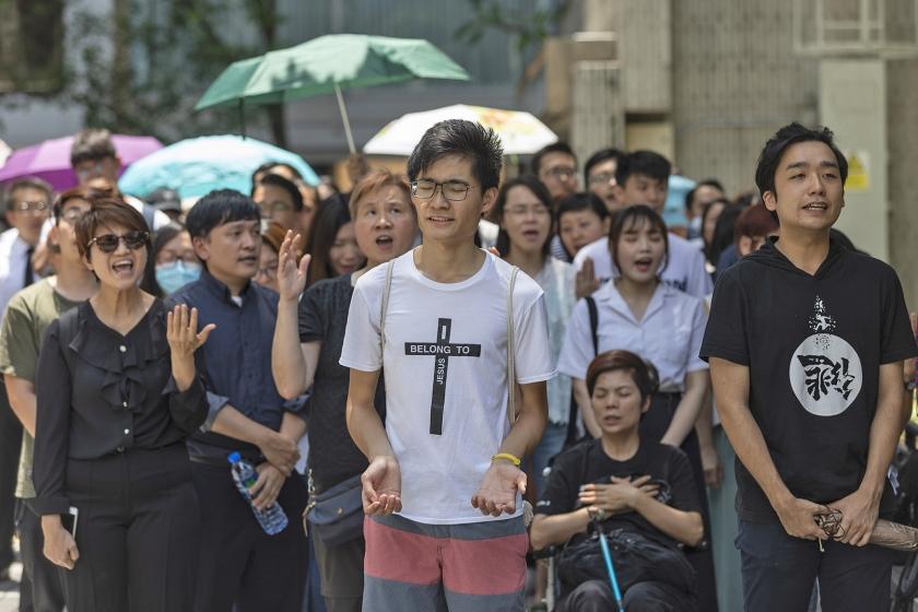 Jonge christenen laten via het zingen van lofzangen weten dat ze het pertinent oneens zijn met de wet die het uitleveren van verdachten aan de autoriteiten op het Chinese vasteland makkelijker maakt.  (epa / Jerome Favre)