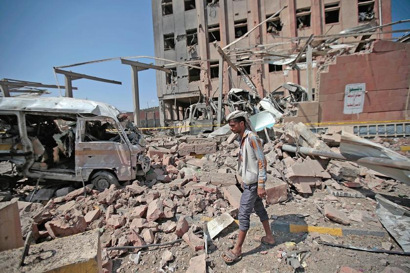 Een man bekijkt de schade die luchtaanvallen van de door Saudi-Arabië geleide coalitie begin februari in de Jemenitische stad Sanaa maakten. Doel van de coalitie is vooral om politieke vrienden daar in het zadel te houden.  (ap / Hani Mohammed)