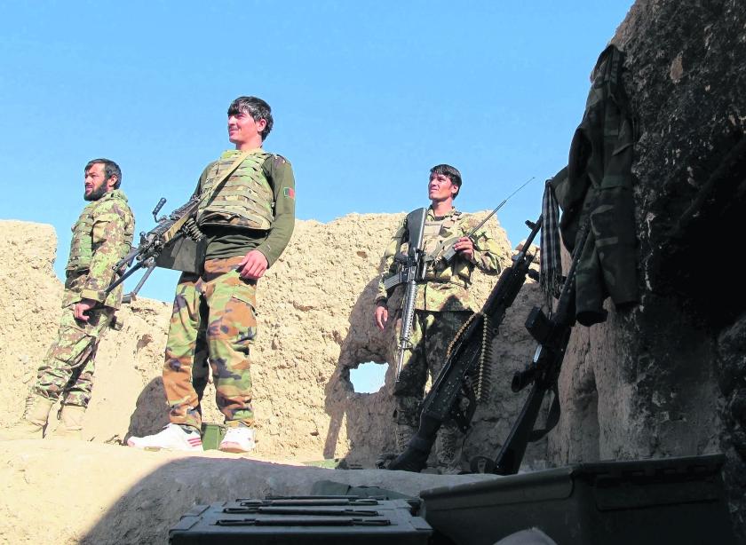 Afghaanse militairen staan op de uitkijk bij een wachtpost in de provincie Helmand. Door de toenemende slagkracht van de taliban krijgen zij het steeds moeilijker. Bij aanslagen van de taliban kwamen de afgelopen dagen tientallen mensen – waaronder ook militairen – om. Ondertussen wil Duitsland de missie in Afghanistan uitbreiden, van 130 naar 980 militairen.  (reuters / Abdul Malik)
